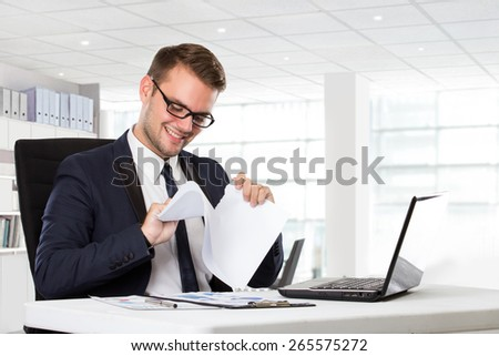 A portrait of a young businessman tearing paper beside in front of laptop