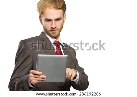 A portrait of a young businessman  with a tablet pc, serious expression, isolated - stock photo