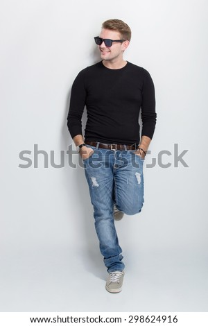 A portrait of a young caucasian man with sunglasses standing leaning on white background - stock photo
