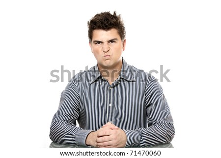 A portrait of a young dissatisfied boss sitting in his office against white background