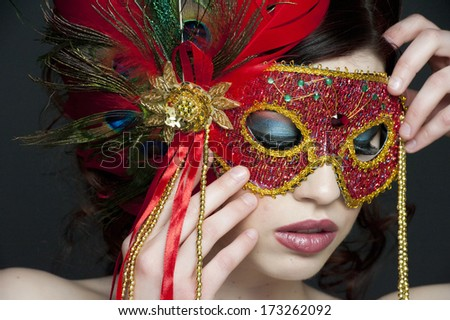 A portrait of a young female masked in a studio.
