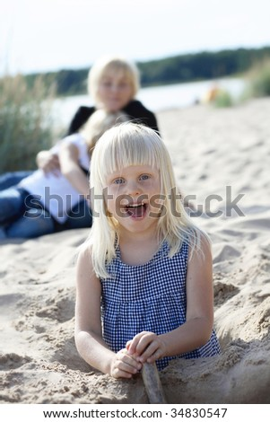A portrait of a young girl having fun at the beach with her mother and sister in the background.