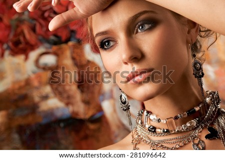 A portrait of a young glamorous woman wearing stylish necklace and pierced earrings. - stock photo