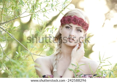 A portrait of a young gorgeous blonde girl looking up with her hand on her cheek while wearing a red flower crown with a flowery top with the sun shining behind her. - stock photo