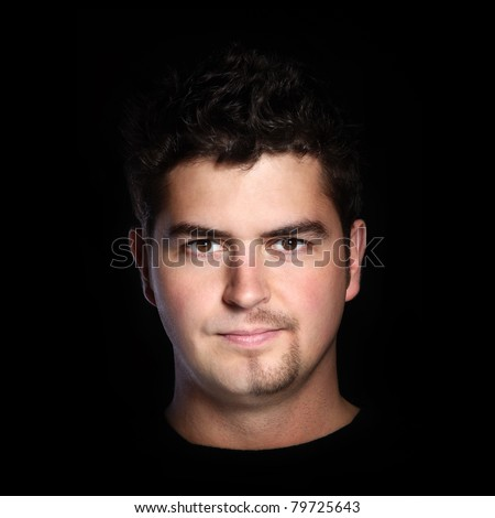 A portrait of a young handsome man with beard partially shaved over black background - stock photo
