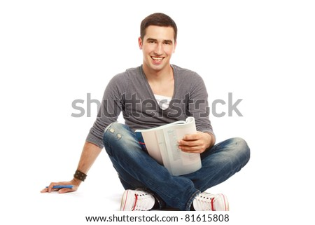 A portrait of a young handsome student sitting on the floor and studying, isolated on white