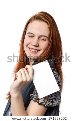 A portrait of a young happy woman holding big white card over white background - stock photo
