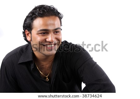 A portrait of a young Indian man wearing a black shirt and gold chain, on white studio background. - stock photo