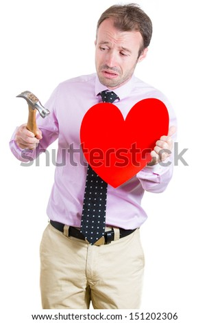 A portrait of a young man desperate,sad, about to cry, holding a hummer and a heart in his hands,isolated on a white background. Relationship, divorce, separation, broken love concept. - stock photo