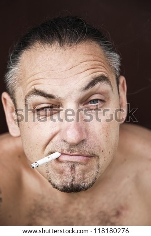 A portrait of a young man smoking a cigarette