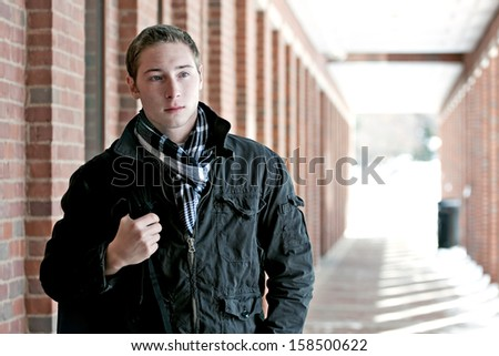 A portrait of a young man standing in an outdoor corridor with his backpack. - stock photo