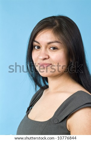 A portrait of a young, naturally beautiful Hispanic woman taken against a blue background. - stock photo