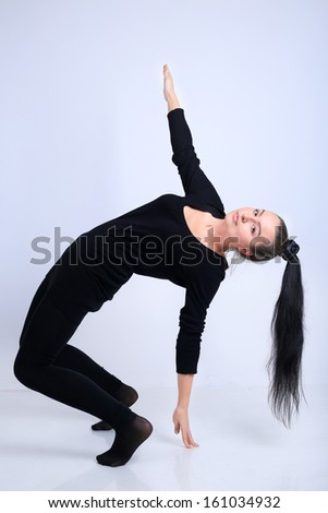 A portrait of a young sexy beautiful brunette woman model with a long hair in ponytail in black clothes on a white background