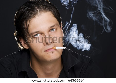 A portrait of a young sexy man smoking a cigarette - stock photo