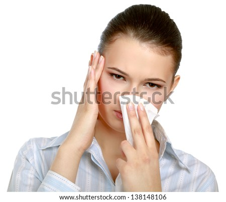 A portrait of a young woman blowing her nose over white background