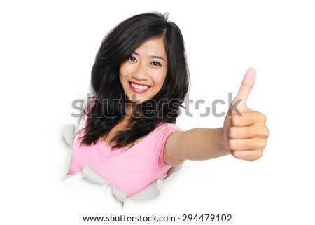 A portrait of a young woman looking through paper rip on white background, showing thumb up - stock photo