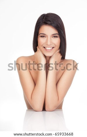 a portrait of a young woman, posing on a white background. she has both her elbows resting on a white table. her hands are around her neck, she has a wide smile and a relaxed face expression. - stock photo