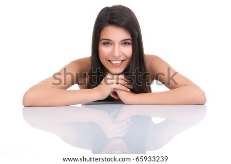 a portrait of a young woman, posing on a white background. she has her arms on a white table and resting her head on her hands. she has a wide smile and a relaxed face expression. - stock photo