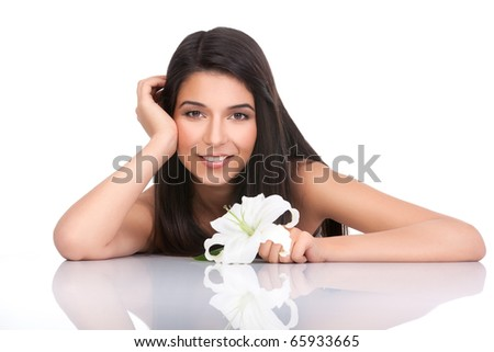 a portrait of a young woman, posing on a white background. she has her arms on a white table and resting her head on one of her hands. she is smiling and she holds a lily in her other hand. - stock photo