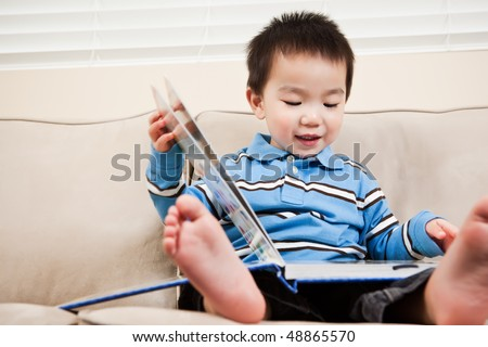 A portrait of an asian boy reading a book - stock photo