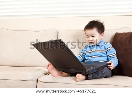 A portrait of an asian boy using a laptop