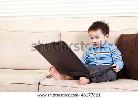 A portrait of an asian boy using a laptop - stock photo