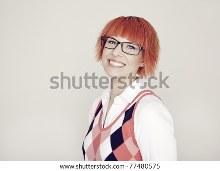 A portrait of an attractive girl with red hair and glasses wearing a argyle vest