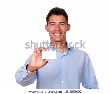 A portrait of an attractive hispanic man holding a blank business card while smiling at you on isolated background - copyspace