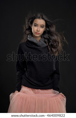A portrait of an attractive young girl wearing black sweater and pink skirt on black background