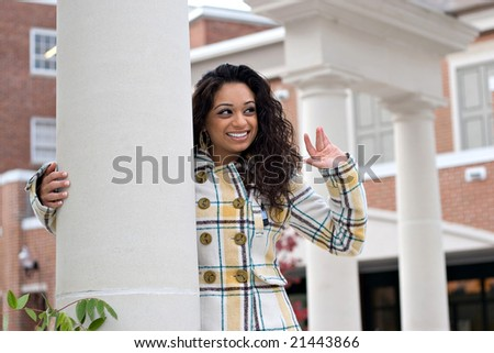 A portrait of an attractive young Indian woman leaning against a pillar and waving to some friends. - stock photo