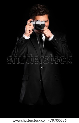 A portrait of an elegant young photographer taking pictures over black background