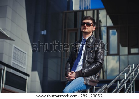 A portrait of an elegantly dressed man in a leather jacket, shirt, tie, jeans, glasses, with a fashionable goatee on the background of the business. The Life Of The City.
