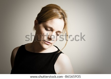 A portrait of an elegantly dressed young, attractive caucasian woman with her eyes closed and her head down. - stock photo