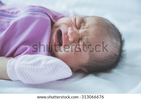 A portrait of an one week old crying baby in a blanket - stock photo