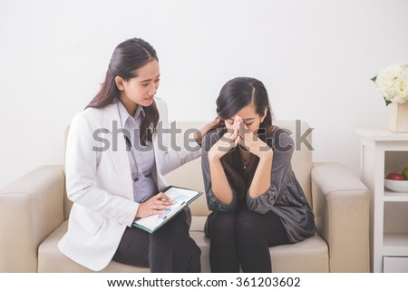 A portrait of Asian female patient crying while consulting her health problem with a female doctor - stock photo