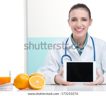 A portrait of cheerful health-care professional promoting healthy eating - stock photo