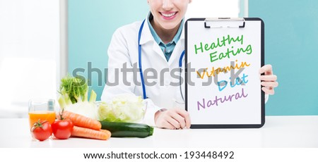 A portrait of cheerful healthcare professional promoting healthy eating - stock photo