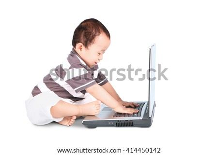 A portrait of cute baby boy typing on laptop computer, isolated on white background - stock photo
