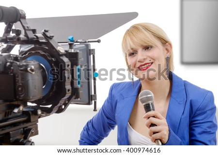 a portrait of elegant blonde woman TV reporter, who is smiling and looking at the camera