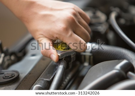 A portrait of hand open radiator pressure cap of car's engine - stock photo