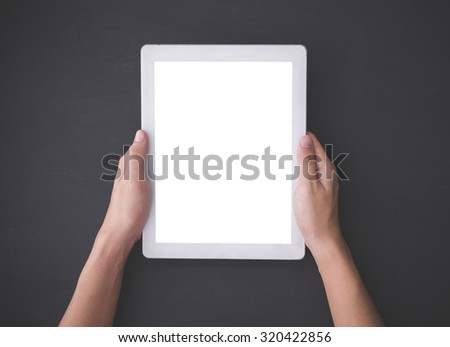 A portrait of Hand using a tablet pc,  on blackboard background, mock up