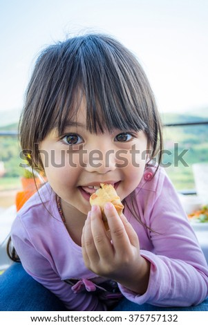 A portrait of long hair pretty little girl eating crispy spring roll laying on mother and blurry mountain and sky background - stock photo