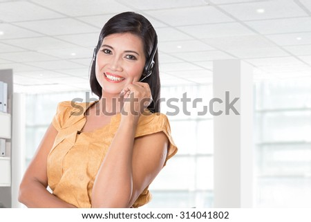 A portrait of middle aged Asian woman using a headset, smiling at the camera - stock photo