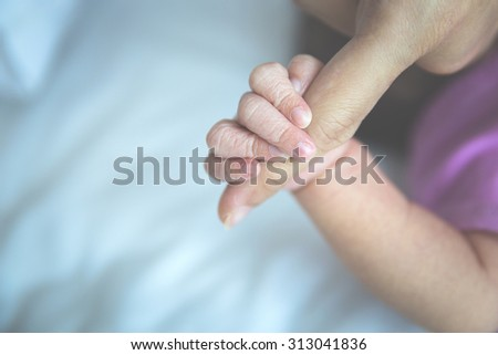 A portrait of newborn baby finger holding her mother, close up - stock photo