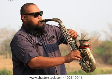 A portrait of saxophone player in the park - stock photo