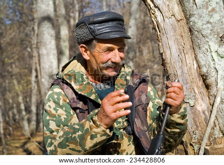 A portrait of the hunter in camouflage in autumn forest. - stock photo