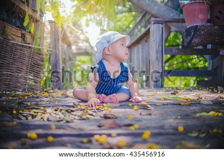 A portrait of the smiling baby boy playing outdoors with vignetting lens. - stock photo