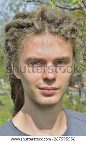 A portrait of the young man with Afro hairdo on nature. - stock photo