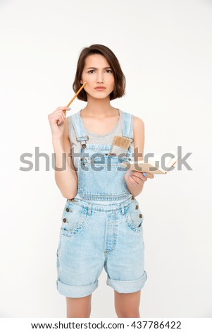 A portrait of thinking young beautiful girl, in gray shirt and denim overall, holding notebook, looking at camera, isolated on white background - stock photo