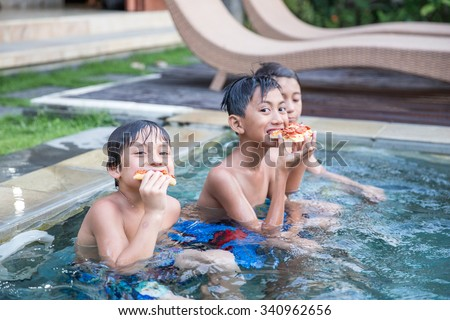 A portrait of three boys enjoying the pool while eating pizza - stock photo